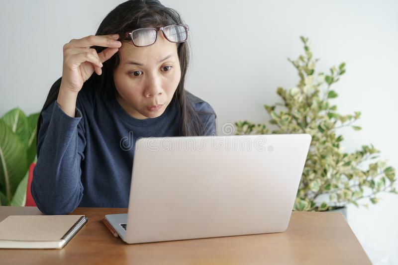 This asian woman is working on laptop in the office . On her face are expression surprise and happy to job success royalty free stock photo