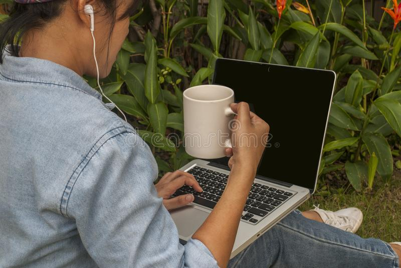 Women are using laptops in the garden. Asian woman working with laptops in the park on holidays And having a cup of coffee in her hand stock photography