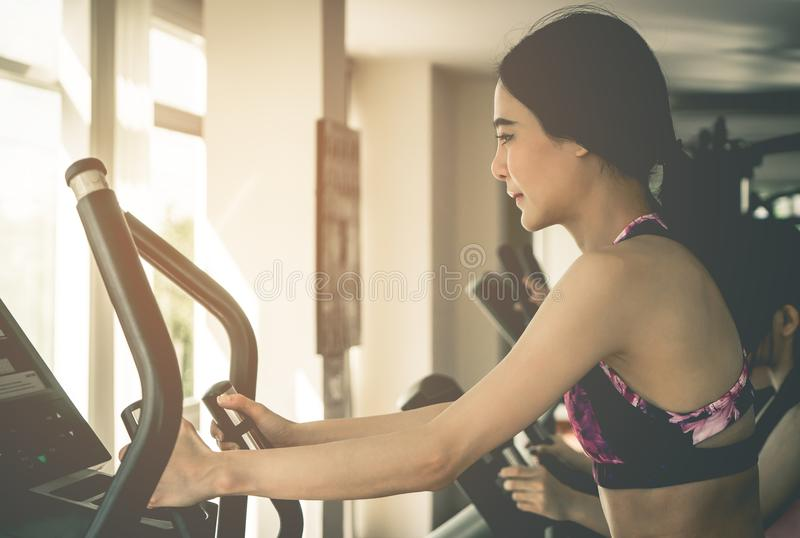 Asian woman working out in fitness gym machine royalty free stock photography