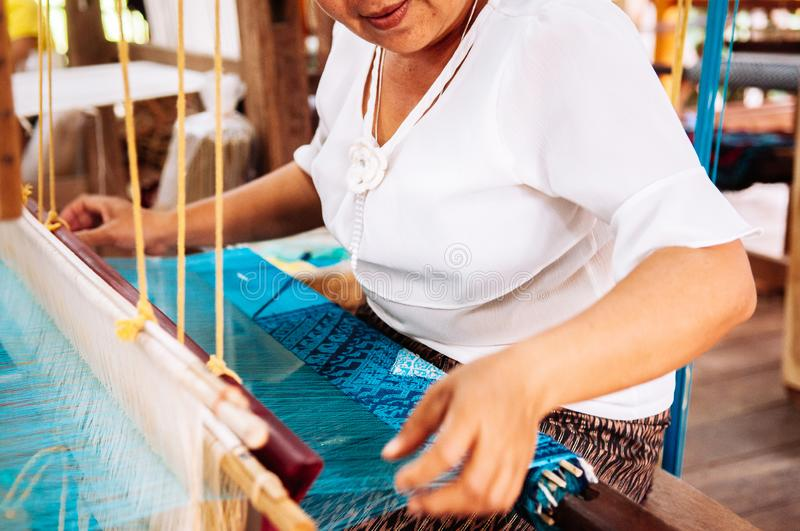 Asian Woman working on Vintage Laos style wooden weaving loom with silk fiber royalty free stock photos
