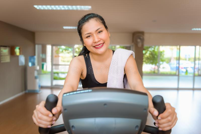 Asian woman workout on cycling in fitness gym., Sports and healthy concept stock images