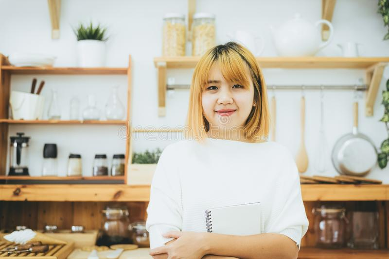 Asian woman write shopping lists in notepad by pen on her kitchen counter at home. Asian woman write shopping lists in notepad by pen on her kitchen counter at royalty free stock images