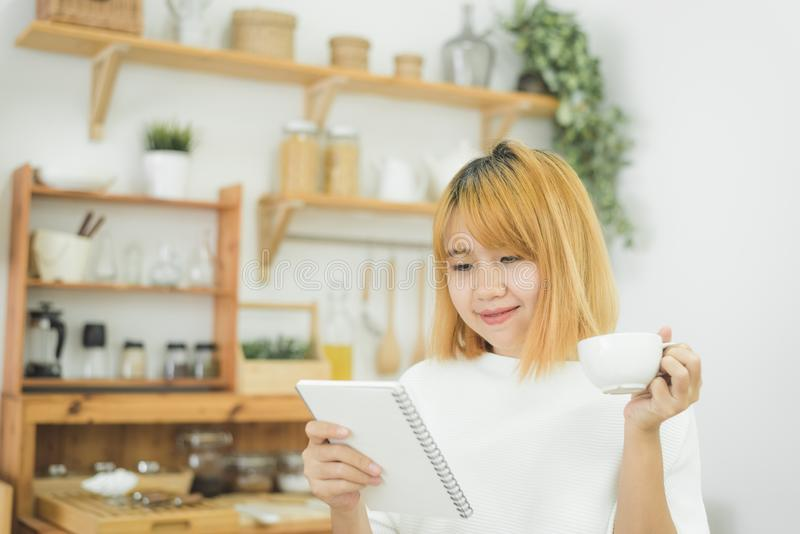 Asian woman write shopping lists in notepad by pen on her kitchen counter at home. Asian woman write shopping lists in notepad by pen on her kitchen counter at royalty free stock photos