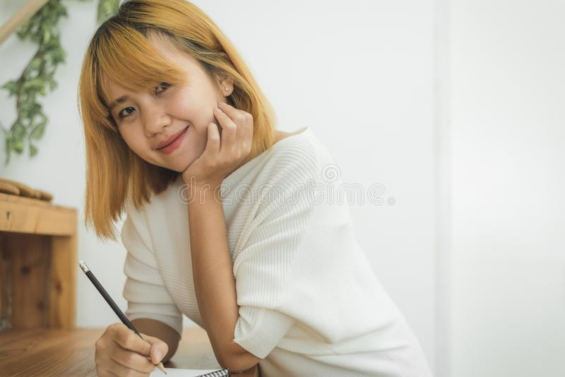 Asian woman write shopping lists in notepad by pen on her kitchen counter at home. Asian woman write shopping lists in notepad by pen on her kitchen counter at royalty free stock photography
