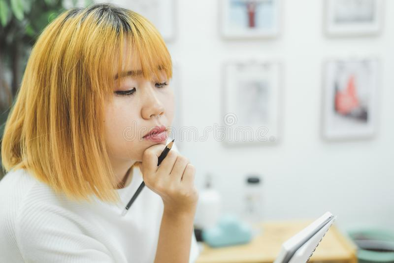 Asian woman write shopping lists in notepad by pen on her kitchen counter at home and reading and tries to remember. Asian woman write shopping lists in notepad royalty free stock photo
