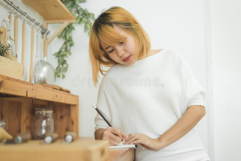 Asian woman write shopping lists in notepad by pen on her kitchen counter at home and reading and tries to remember. Asian woman write shopping lists in notepad stock photo