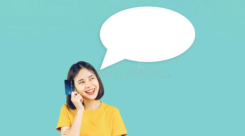 Asian woman yellow casual clothes holding credit card. Asian woman yellow casual clothes holding credit card on light blue background with speech bubble for put royalty free stock photos