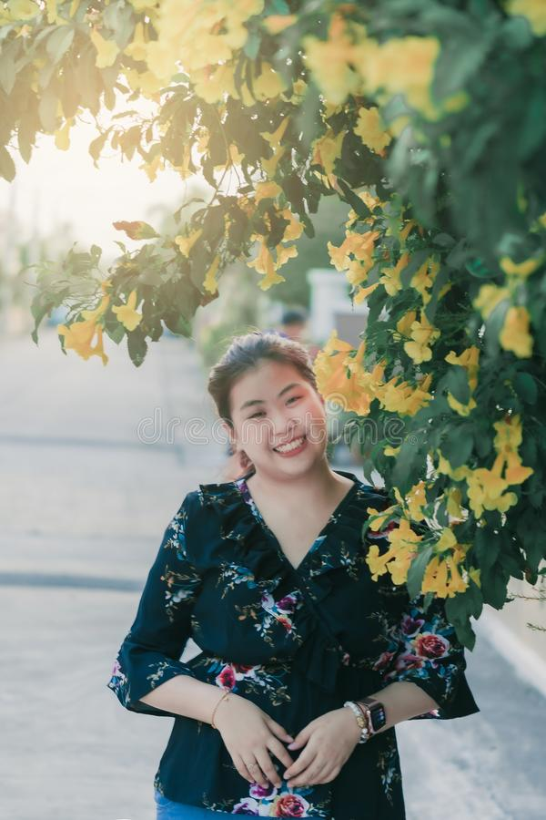 Asian woman with yellow flower and green leaves or leaf blurred background for lifestyle portrait people image.  stock images