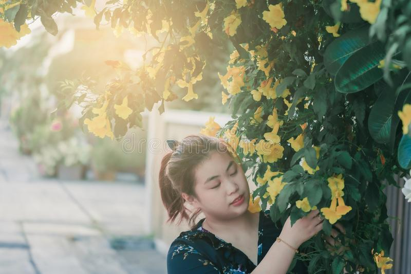 Asian woman with yellow flower and green leaves or leaf blurred background for lifestyle portrait people image.  royalty free stock photo