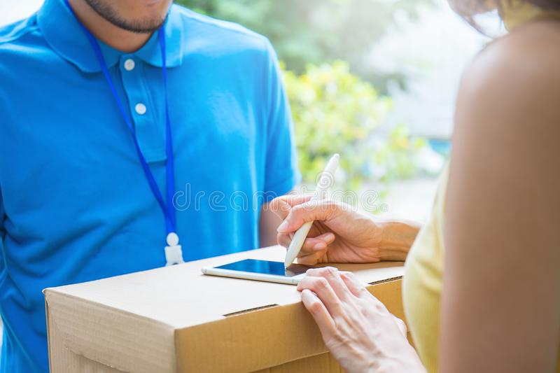 Asian woman accepting receive a delivery of boxes from delivery asian man. Asian women accepting receive a delivery of boxes from delivery asian man, sign and royalty free stock photos