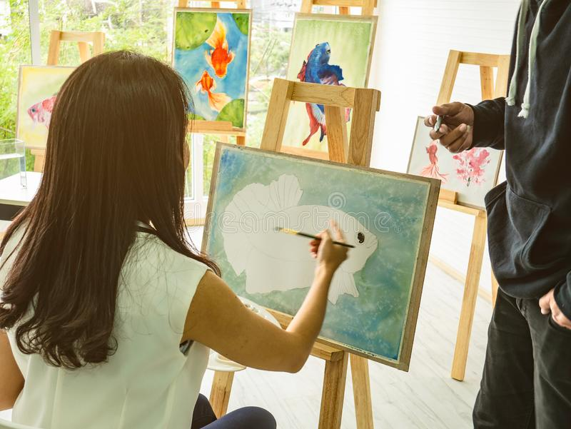 Asian women artrist painting the fish in classroom while her teacher teaching and tutor how to paint royalty free stock images