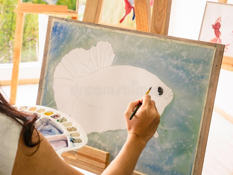 Asian women artrist painting the fish in classroom while her teacher teaching and tutor how to paint stock photo