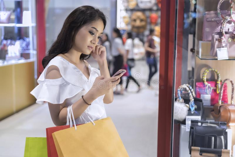 Asian women and Beautiful girl is holding shopping bags and using a smart phone and smiling while doing shopping in stock image