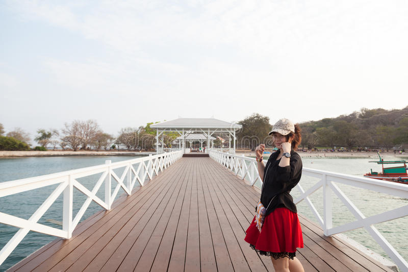 Asian women black shirt. Standing on wooden bridge. Asian woman black shirt. Standing in a white wooden bridge. Beside the sea stock photography