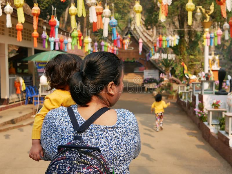 Asian woman carrying and taking her little baby girl to visit a Buddhist temple stock photos
