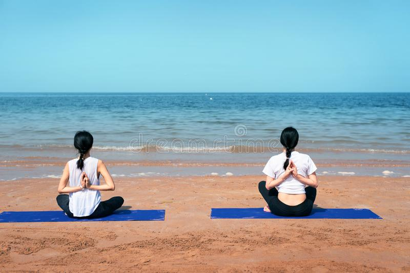 Women doing yoga on the beach. Asian women doing yoga on the beach two friends together girlfriends seaside summer mat sit sitting hands back tangled synchronize royalty free stock photos