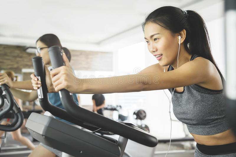 Asian woman with earphones on exercise bike royalty free stock photo