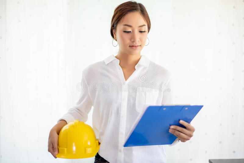 Asian women engineering inspecting and working and holding blueprints at office.she is smiling happy for work. Asian woman engineering inspecting and working and stock photography