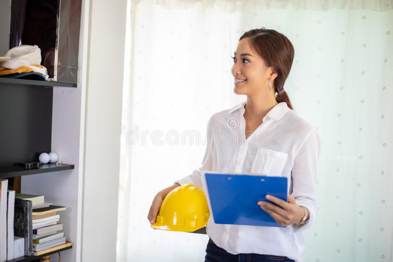Asian women engineering inspecting and working and holding blueprints at office.she is smiling happy for work. Asian woman engineering inspecting and working and stock photos