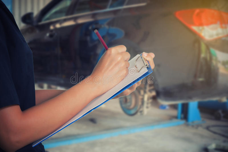 Asian women engineers and technicians are checking mechanic and. Inspecting on a car in auto repair shop the list on the board stock photo