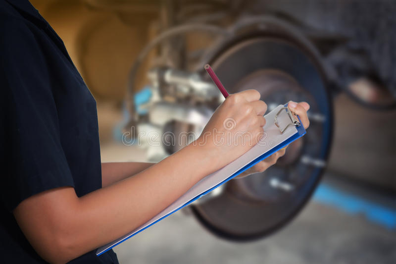 Asian women engineers and technicians are checking mechanic and. Inspecting on a car wheel brake disc and shoes of lifted automobile at repair service station royalty free stock photography