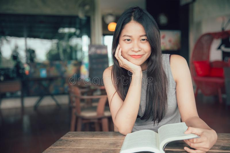 Asian women enjoy smile reading book in holiday looking camera stock photo