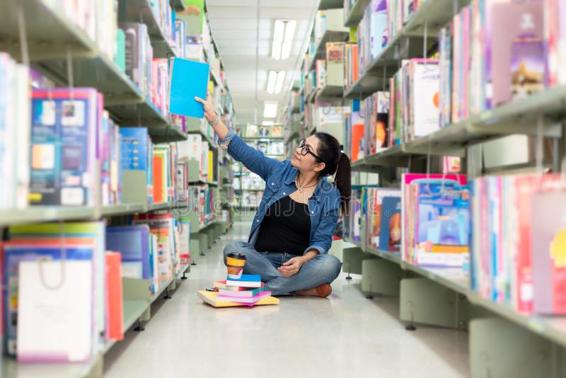 Asian women finding book and reading something in a book,  adult female choosing a book on the bookshelf in a library. stock images
