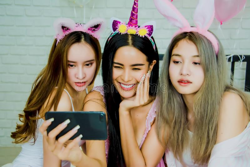 Asian woman friend group,attractive and sexy,Selfie with smartphone ,relax on white bed full of balloons,cheerful and charming, royalty free stock images
