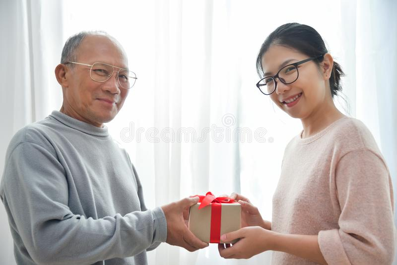Asian woman giving a brown gift box to elderly man. royalty free stock image