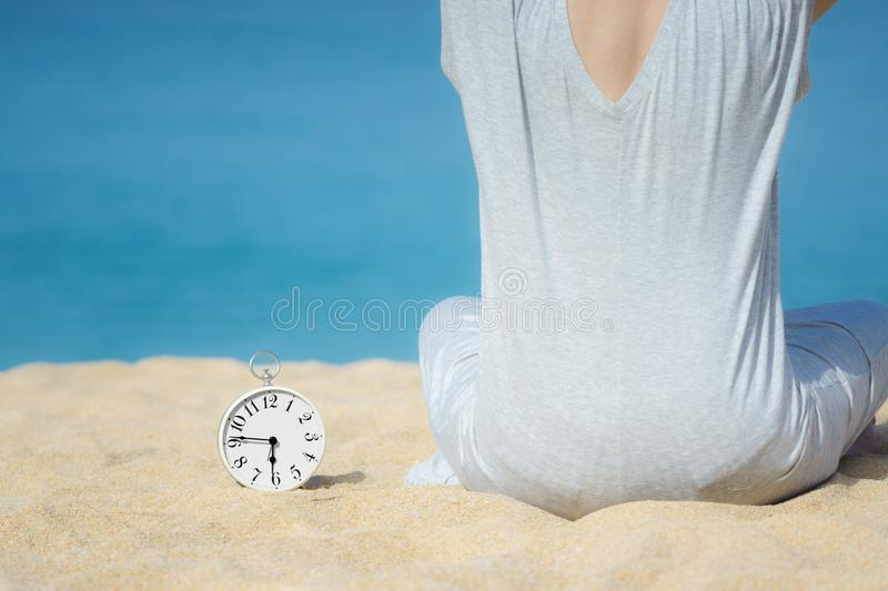 Asian women in a gray dress sitting beside the white alarm clock placed on the sand. Blue sea and sky as a background. Concept for. Asian woman in a gray dress royalty free stock photos