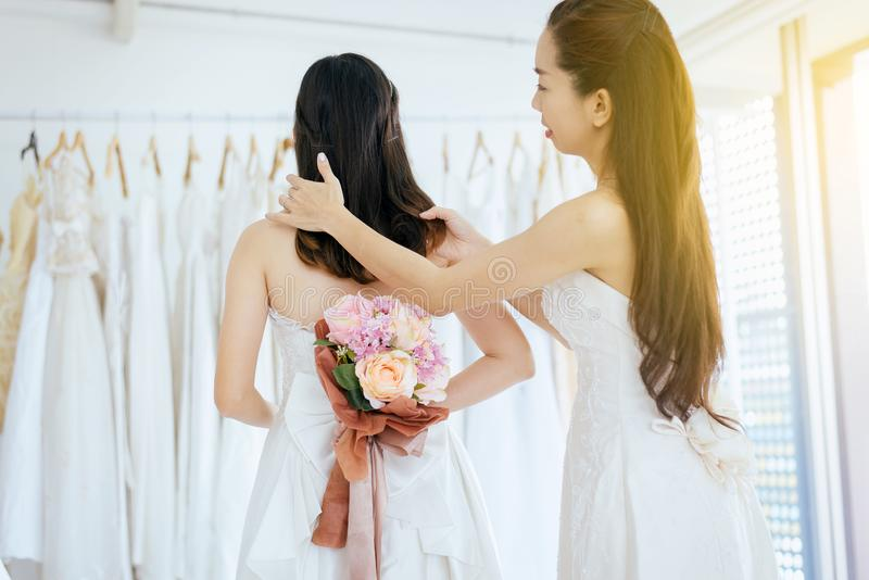 Asian women hairdressing and make up to woman bride on white wedding dress stock photography