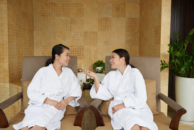 Asian Women Having Wellness Weekend. Best friends in bathrobes having wellness weekend: they sitting on lounge chairs and chatting with each other while waiting royalty free stock photos