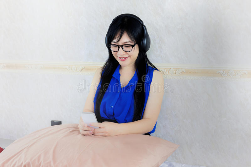 Asian women with headphone sitting and surfing internet on smart royalty free stock image