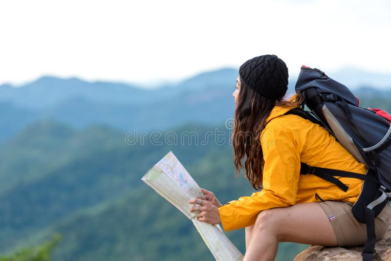 Asian women hiker or traveler with backpack adventure holding map to find directions and sitting relax on the mountain nature f royalty free stock images