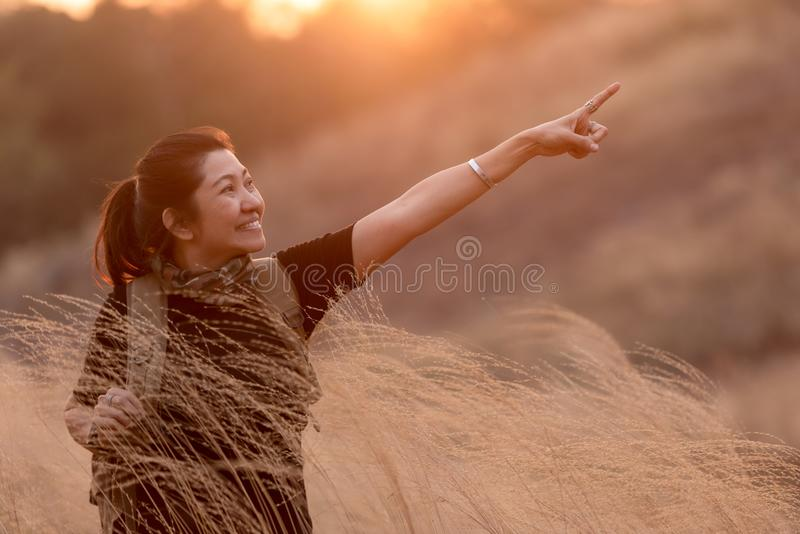 Asian Women hiker or traveler with backpack adventure walking relax and pointing in field meadow  for education and explore nature stock photography