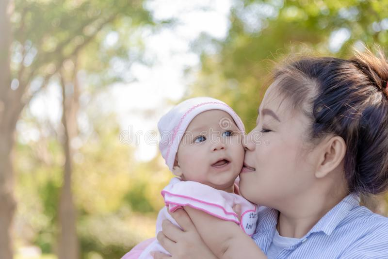 Asian women holding and kissing her little 4 months daughter outdoor royalty free stock image
