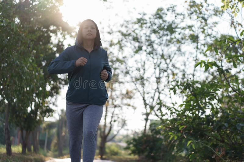 Asian women jogging in the morning garden royalty free stock photography