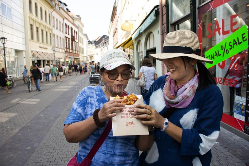 Asian women mother and daughter travel and eating pizza on street stock photography