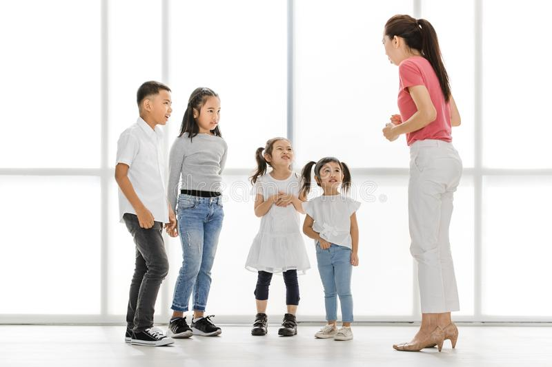 Teacher teaching kids in acting class. Asian women in pink shirt teach Asian girls and boy some acting to act fake cry, they stand in front of big white window royalty free stock photos