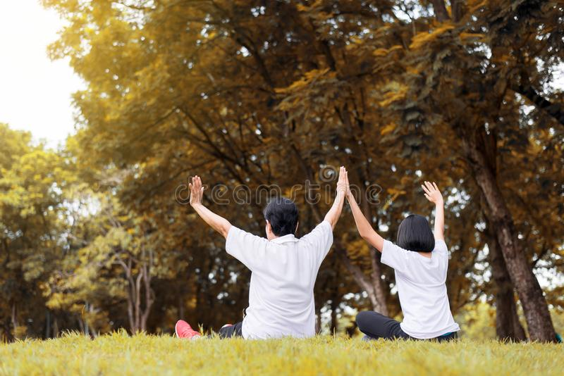 Asian women raise up hands and relax at park in the morning together,Happy and smiling,Positive thinking,Healthy and lifestyle con. Cept royalty free stock photography