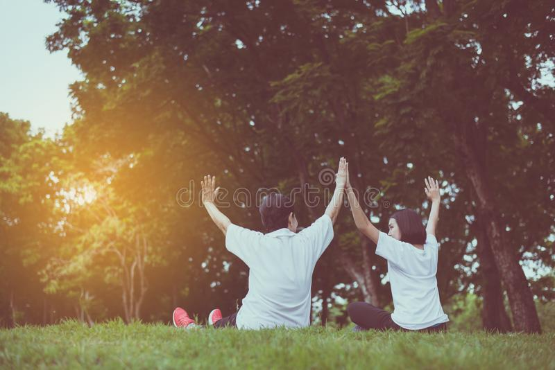 Asian women raise up hands and relax at park in the morning together,Happy and smiling,Positive thinking,Healthy and lifestyle con. Cept royalty free stock photo