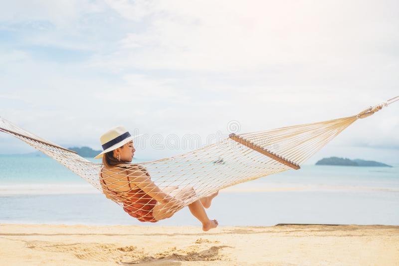 Asian women relaxing in hammock summer holiday on beach stock photo