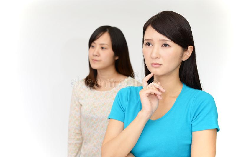 Uneasy Asian women stock images