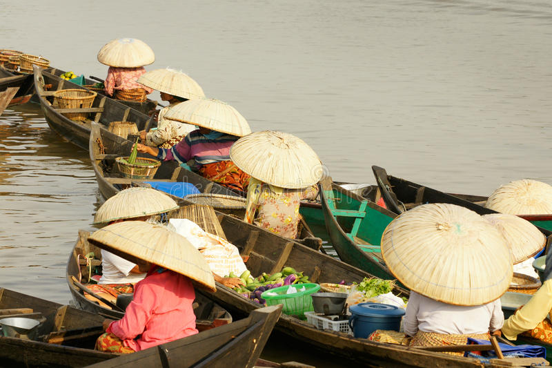 Asian women selling products in their little boats at a floating market on the river in the afternoon. stock photography