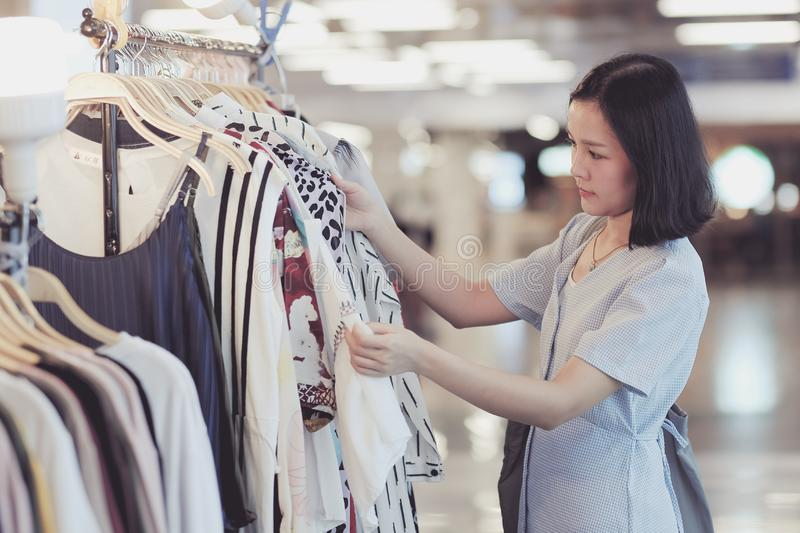 Asian women shopping some dresses in the shopping center royalty free stock image