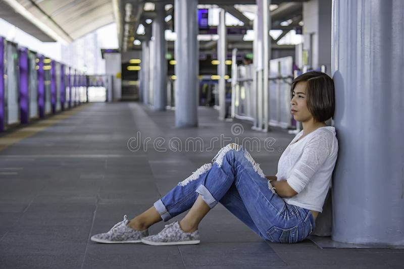 Asian women sit on the floor Background blurry Skytrain station stock image