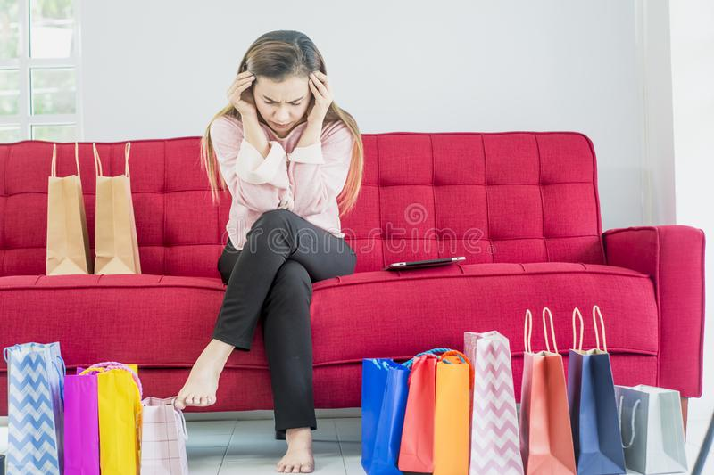 Asian women sit on a red sofa and feel stressed, sad and depressed expression with a lot of colorful shopping paper bags,Concept royalty free stock photography