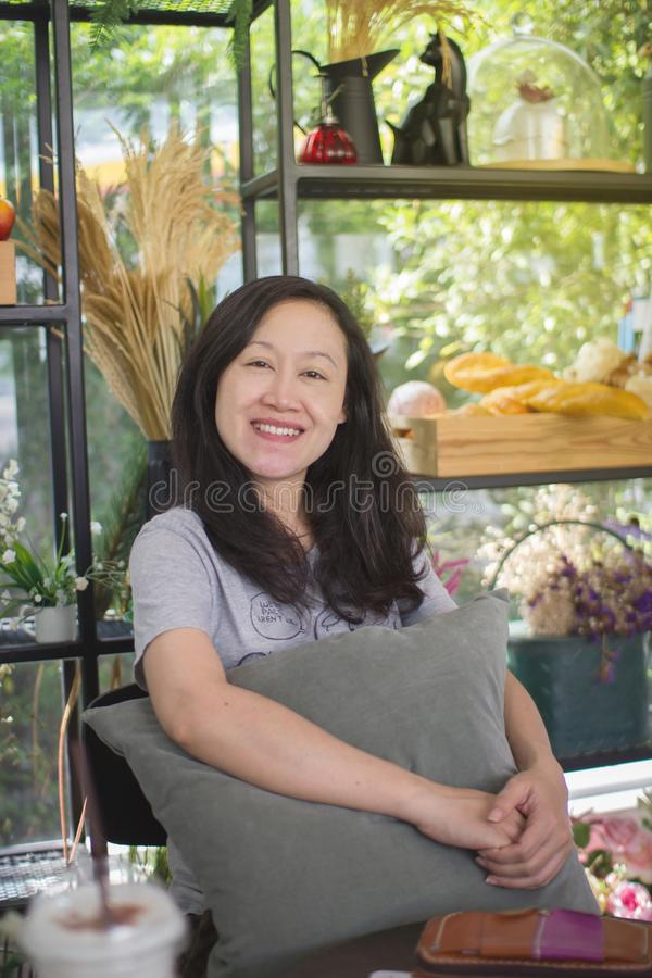 Asian women smile happily. In a coffee shop. stock photos