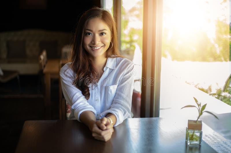 Asian women smiling and happy Relaxing in a coffee shop after working in a successful office. Asian woman smiling and happy Relaxing in a coffee shop after royalty free stock images