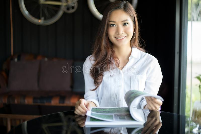 Asian women smiling and reading a book for relaxation at coffee stock photo